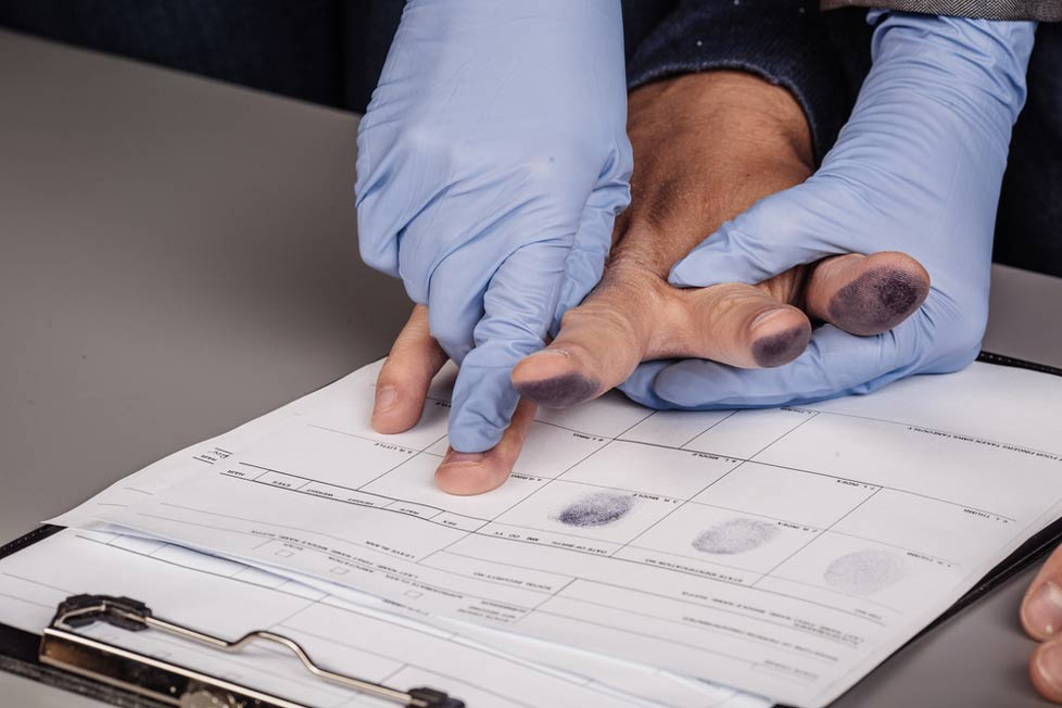 Gloved individual takes fingerprints of another person