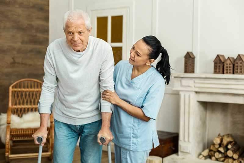 Caregiver helping elderly man walk